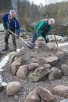 Bau einer Kräuterspirale aus Feldsteinen, Kräuterbeet, Beet, Kräutergarten, Gartenarbeit. Auffüllen mit nährstoffarmen Boden