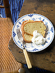 Two slices of pound cake on a plate, with whipped cream