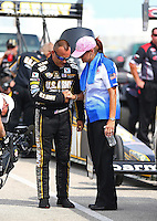Aug. 31, 2013; Clermont, IN, USA: RFC chaplin Linda Smiley prays with NHRA top fuel dragster driver Tony Schumacher during qualifying for the US Nationals at Lucas Oil Raceway. Mandatory Credit: Mark J. Rebilas-