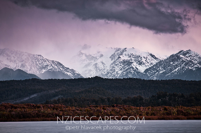 Stormy skies above Southern Alps from Okarito Lagoon at twilight in winter. Franz Josef Glacier just visible in middle, Westland National Park, West Coast, New Zealand