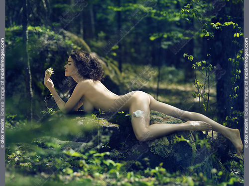 Artistic sensual erotic portrait of a beautiful sexy nude woman with a flower and a garter on her thigh lying naked on rocks in a deep green forest bathing in gentle sunshine