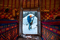 A woman is framed in the door of a yurt putting her skins on her skis while on a ski trip in Kyrgyzstan