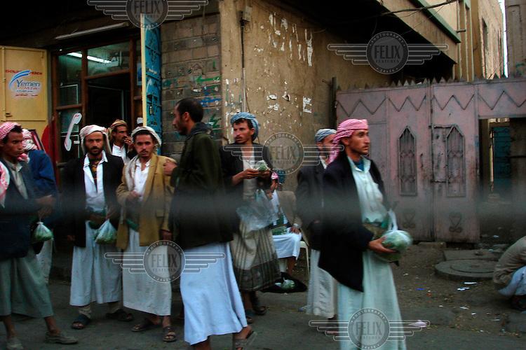Men buy and chew qat, a mildly hallucinogenic plant that is very popular in Yemen.