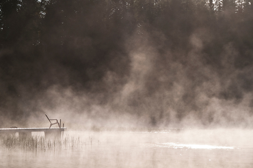 Morning mist shrouds the dock and an Adirondack chair at Republic Island Cottage along the Michigamme River near Republic Michigan.