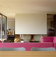 The open-plan living area is separated from the kitchen by a large fireplace and furnished with a pink sofa original to the house