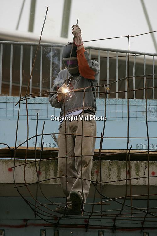 """Foto: VidiPhoto..ARNHEM - Burgers' Zoo krijgt nieuwe rotsen. Het Arnhemse dierenpark bouwt op dit moment zogenoemde """"kopjes""""; granieten rotsformaties die als eilanden op de uitgestrekte graslanden van de Oostafrikaanse savanne zijn te vinden. Deze """"kopjes"""" worden door medewerkers van een constructiebedrijf uit Limburg nagemaakt door een geraamte van betonstaal te vervaardigen. Later worden deze met pur gedicht en vervolgens krijgen ze met spuitbeton een rotsachtig uiterlijk. De """"kopjes"""" zijn onderdeel van een groot stallencomplex dat in totaal zo'n 8000 vierkante meter beslaat als het klaar is."""