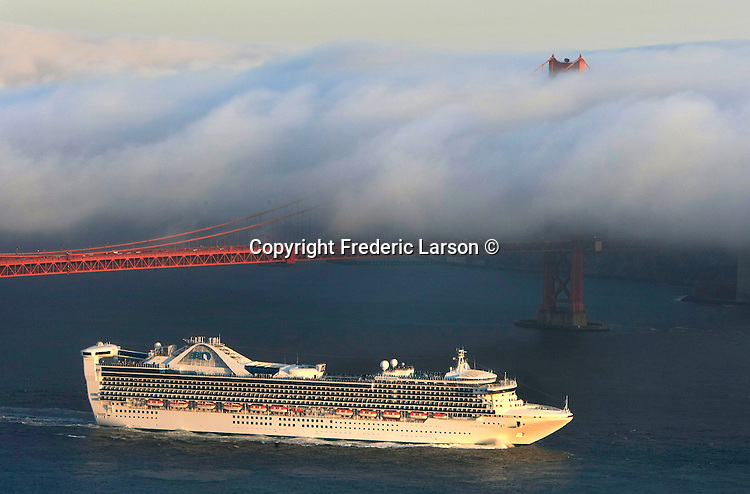 The San Francisco fog creeps over the deck of the Golden Gate Bridge as a cruise ship sails out of the bay at dusk.