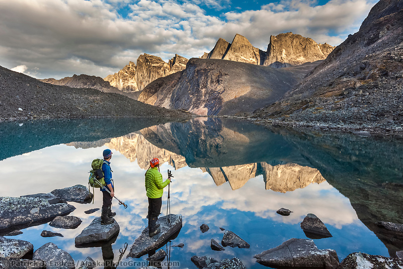 Hikers view Camel peak reflecting in a mountain lake in the Arrigetch Peaks, Gates of the Arctic National Park, Alaska.
