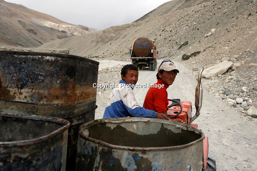 "China started building a controversial 67-mile ""paved highway fenced with undulating guardrails"" to Mount Qomolangma, known in the west as Mount Everest, to help facilitate next year's Olympic Games torch relay./// Two workers gather water and bring it to the construction site on the road to EBC. <br /> Tibet, China<br /> July, 2007"
