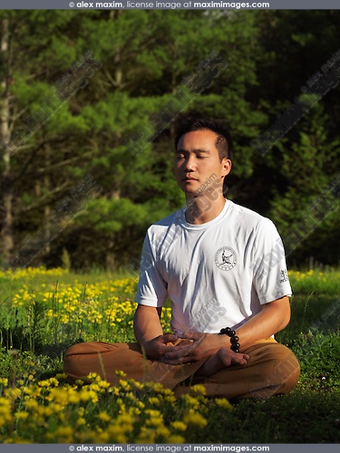 Toronto Shaolin school instructor Dao meditating outdoors during sunrise in the nature, sitting with crossed legs in green outdoor summer nature scenery. Buddhist meditation. Instructor Shi Chang Dao, Toronto Shaolin Temple STQI.