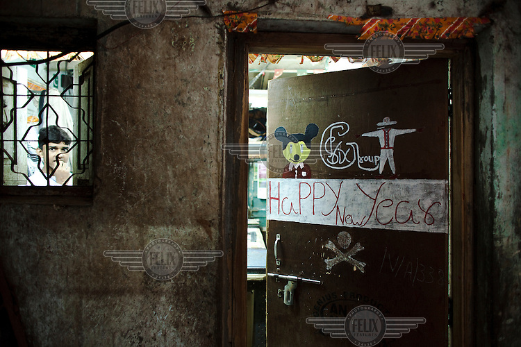Entrance to a workshop in Dharavi slum with New Year greeting.