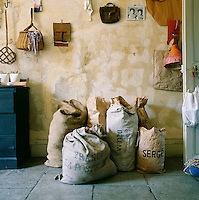 A collection of sacks and paper bags makes a rustic arrangement standing against this wall, which has a distressed finish