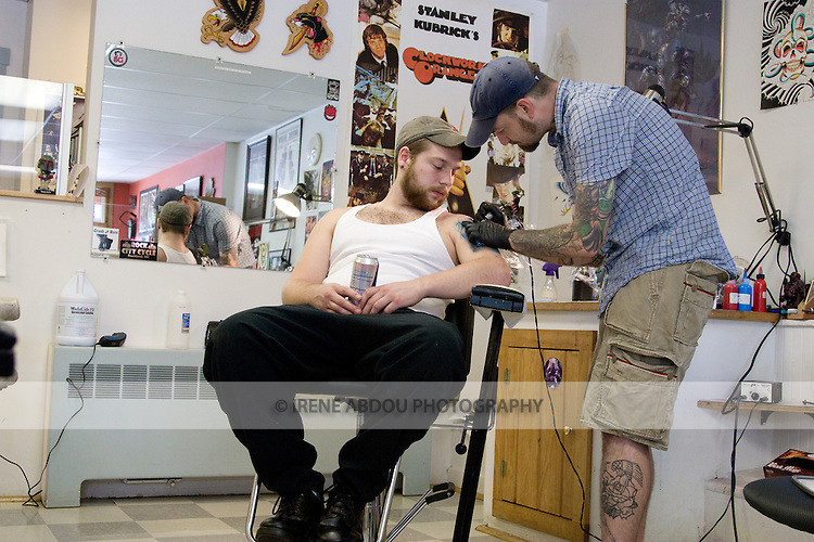 A man gets a tattoo at a tattoo parlor in rural Maine.