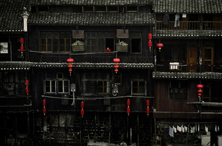 A man leaning out of the window in the ancient town of Fenghuang in the Hunan Province, China.