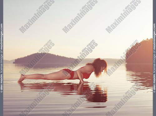 Young woman practicing Hatha yoga on a floating platform in water on the lake during misty sunrise in the morning. Yoga or pilates Plank posture, Kumbhakasana, Chaturanga push up. Muskoka, Ontario, Canada.