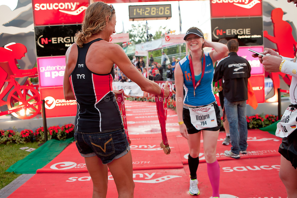 Chrissie Wellington giving our medals to late finishers after winning the Challenge Roth Ironman Triathlon, Roth, Germany, 10 July 2011