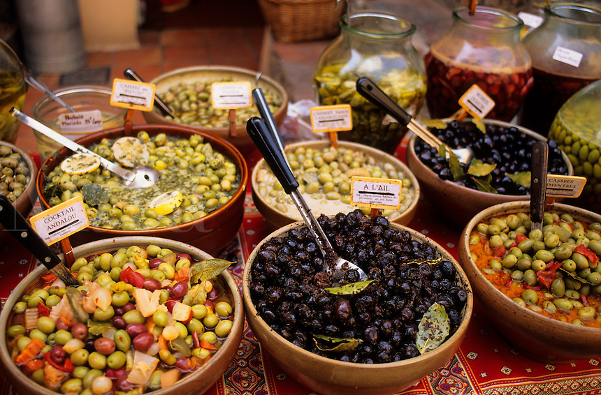 Assortment of varieties and treatments of olives displayed for sale on a market stall, Provence, France.