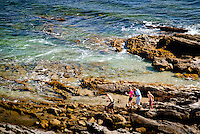 Visitors Of Laguna Beach Walking On The Rocks At The Beach