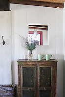 A flower arrangement and green mugs are placed on a wooden cupboard standing against white tongue and groove panelling.