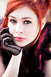 Close up of redheaded female youth wearing a black lace glove looking into camera