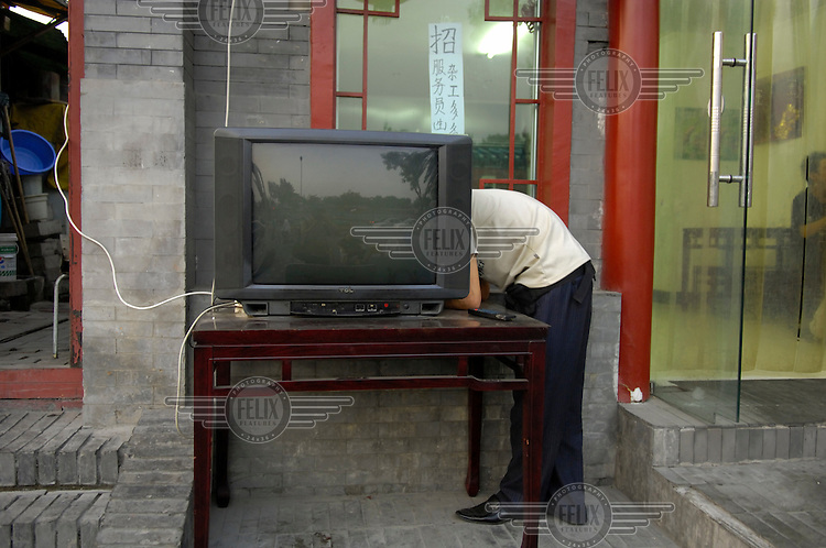 A restaurant worker sets up a TV on an outdoor table. Up to fifty TV channels, all state controlled, are available in Beijing.