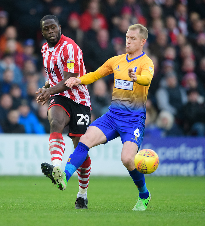 Lincoln City's John Akinde vies for possession with Mansfield Town's Neal Bishop<br /> <br /> Photographer Chris Vaughan/CameraSport<br /> <br /> The EFL Sky Bet League Two - Lincoln City v Mansfield Town - Saturday 24th November 2018 - Sincil Bank - Lincoln<br /> <br /> World Copyright © 2018 CameraSport. All rights reserved. 43 Linden Ave. Countesthorpe. Leicester. England. LE8 5PG - Tel: +44 (0) 116 277 4147 - admin@camerasport.com - www.camerasport.com