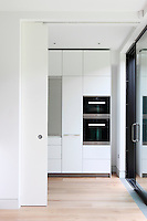 A view past an open sliding door to a modern white ktichen with an integral double oven.