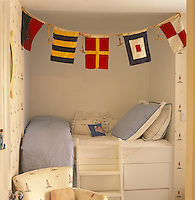 A small boy's bedroom has a raised mattress above sets of deep drawers in a contemporary bunk bed and is decorated with early 20th century sailing signal flags