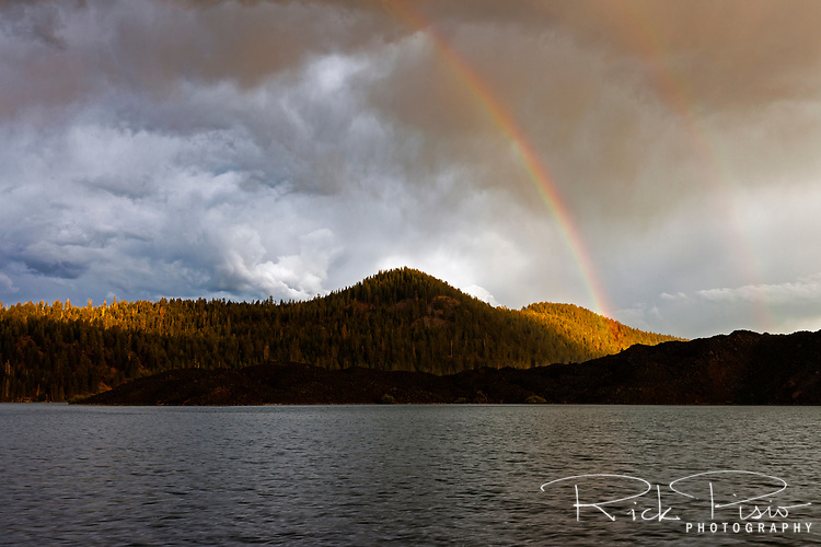 A rainbows arc rises above the lava field on the south shore of Butte Lake in Lassen Volcanic National Park.