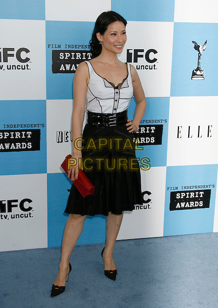 LUCY LIU.The 2007 Independent Spirit Awards held at the Santa Monica Pier, Santa Monica, California, USA..February 24th, 2007.full length black skirt white top red clutch purse hand on hip .CAP/ADM/RE.©Russ Elliot/AdMedia/Capital Pictures