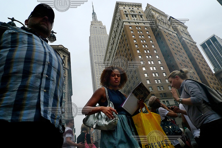 People walk along 34th Street in Manhattan, New York City. In the background is the Empire State building.