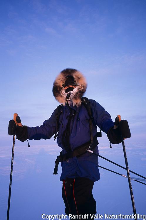 Mann med trekker pulk en kald dag. ---- Man pulling sled a cold day.