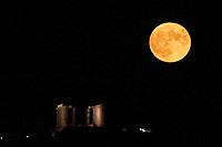 The full moon rises over the ancient Temple of Poseidon in Sounion, south-east of Athens, Greece. Thursday 15 August 2019