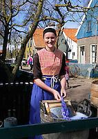 Enkhuizen Zuiderzeemuseum. Vrouw wast een theedoek in een wastobbe bij de huisjes uit Urk