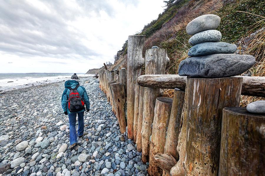 Woman walking along seawall on North Beach, Port Townsend, Jefferson County, Washington State, USA