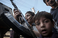 A Syrian youths chant anti government slogans as one of them holds a weapon during a demostration after friday prayers in the Bustan Al Qasr district of Aleppo, Syria.
