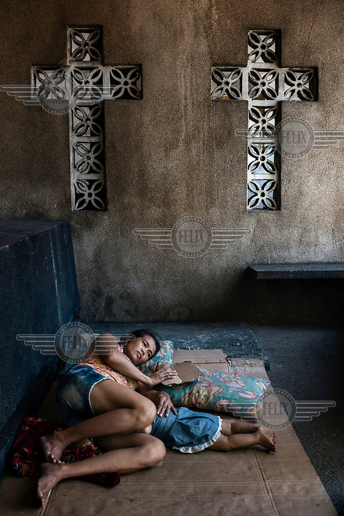 Noemi Canilang, 41, rests beside a tomb with her grandson John Lewis de la Cruz, eight months, in the Espiritu family mausoleum, in Manila North Cemetery, which she is paid to look after by the family and therefore is allowed to sleep in with five other members of her family.  Manila North Cemetery is home to thousands of 'informal settlers' who have built shacks using in and around the mausoleums, crypts and tombs. In comparison to the city's dangerous shantytowns the cemetery is relatively quiet and safe. However, water must be collected from a few public wells and the electricity supply is erratic, usually stolen from mains cables. In the summer the sweltering heat drives people to sleep outside often on top of the tombs.<br /> <br /> Some of the residents live in the crypts and mausoleums of wealthy families, who pay them a stipend to clean and watch over them. Others make a living carving headstones or selling candles to visitors and helping out at funerals as the daily life of the cemetery goes on around the people who live there.