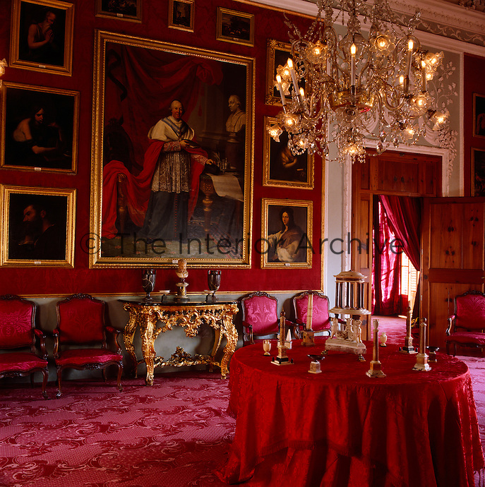 Red damask lines the walls and covers the furniture in this dramatic salon which features gilt-framed family portraits and artwork on the walls