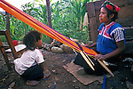 An indigenous Tzotzil woman and her sister, who were expelled from her community of San Juan Chamula for being evangelical, as opposed to Catholic, weaves on a backstrap loom in her neighborhood of La Hormiga, above San Cristobal de las Casas, Chiapas,Mexico.