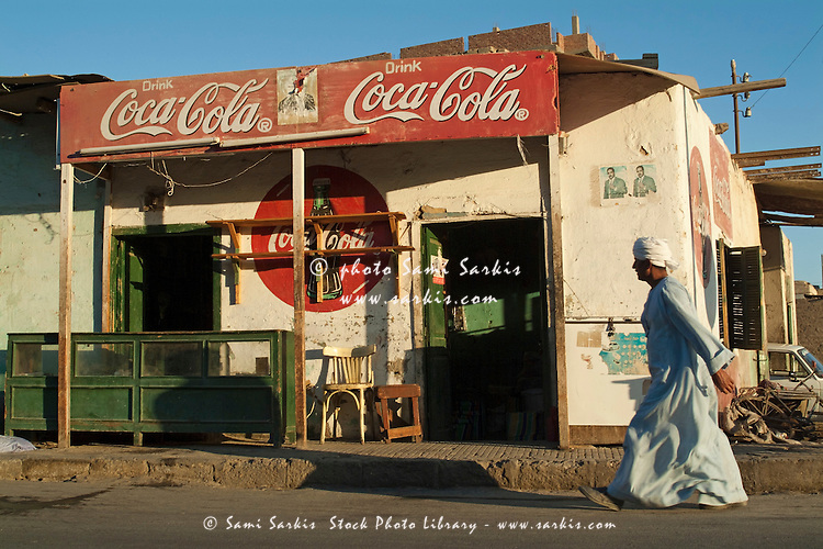 Man dressed in traditional Islamic dress walks by a coffee shop, Quoseir Village, Red Sea, Egypt.