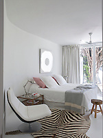 The contemporary whitewashed bedroom has floor-to-ceiling sliding glass doors that overlook the garden