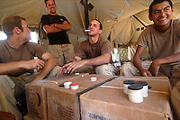 "Soldiers play cards on top of ""Meals Ready to Eat"" boxes in the desert near Rawah, Iraq. Thursday August 4, 2005."