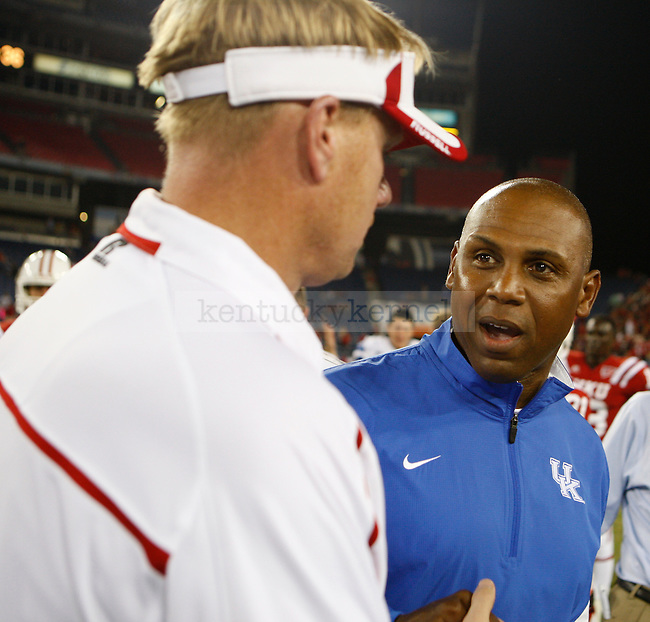 Head football coach of the University of Kentucky football team spoke with a member of WKU athletics staff after the game on Thursday, September 1, 2011, in Nashville, Tennessee.  It was considered a home game for the Hilltoppers at LP Field. Photo by Latara Appleby | Staff