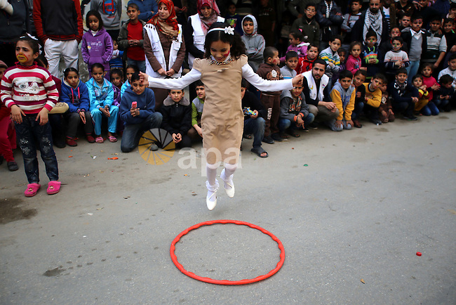 A Palestinian girl plays during a street game organised by volunteers of the Friday of Joy Initiative, in al-Shati refugee camp, in Gaza city, February 6, 2015. Ten Palestinian volunteers organise street games, painting and drama, every Friday afternoon in the streets of  refugee camps and provide outlets for the children's energy with organised games, dancing and singing, which gives extra psycho-social support to vulnerable children. Photo by Khaled al-Sabbah