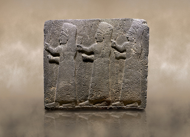 Photo of Hittite monumental relief sculpted orthostat stone panel of a Procession Basalt, Kargamis, Gaziantepe, 900 - 700 B.C. Anatolian Civilisations Museum, Ankara, Turkey.<br /> <br /> It is a depiction of three marching female figures in long dress with a high headdress at their head. These women are considered to be the nuns of the Goddess Kubaba. The figures in the front and behind have a bunch of spicy in their right hand while the figure in the middle has an empty right hand. Figures carry objects similar to a sceptre in their left hand.<br /> <br /> Against a brown art background.