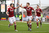 James Collins of Northampton Town (centre) celebrates scoring the opening goal against Morecambe during the Sky Bet League 2 match between Northampton Town and Morecambe at Sixfields Stadium, Northampton, England on 23 January 2016. Photo by David Horn / PRiME Media Images.