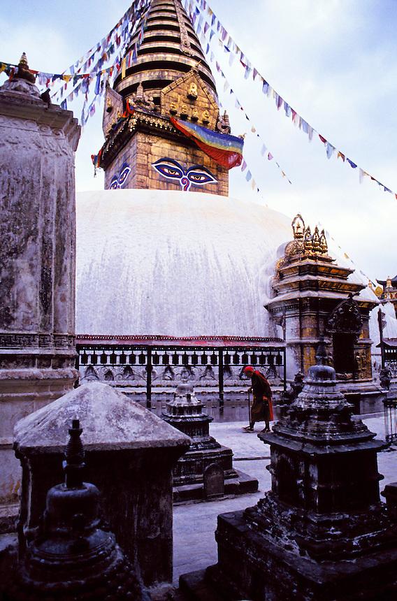 """Swayambhunath, also known as the Monkey Temple. A Buddhdist """"stupa"""" (shrine) outside Kathmandu. Buddhist monk walks around in clockwise, traditional fashion. Kathmandu, Nepal Asia."""