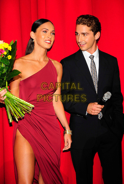 "MEGAN FOX & SHIA LaBEOUF.""Transformers: Revenge Of The Fallen"" premiere, Cinestar Sony Center, Berlin, Germany..June 15th, 2009.half length black suit La Boeuf pink red dress one shoulder slit split thigh leg flower bouquet microphone .CAP/PPG/NK.©Norbert Kesten/People Picture/Capital Pictures"