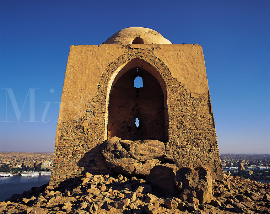 Simple Islamic memorial or shrine on a hilltop above the river Nile and the city of Aswan, Egypt. River and town visible behind the shrine, under a blue sky