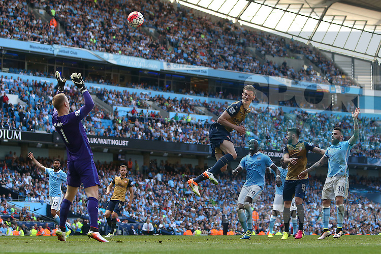 Arsenal's Laurent Koscielny sends a header over Joe Hart of Manchester City and on to the cross bar during the Barclays Premier League match at the Etihad Stadium. Photo credit should read: Philip Oldham/Sportimage